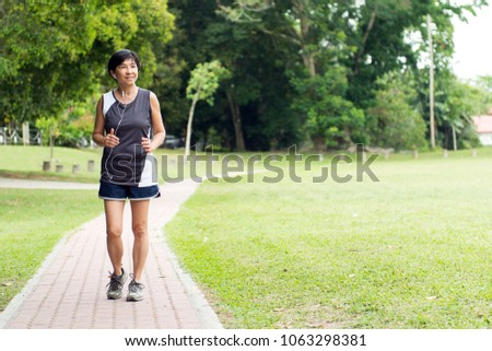 Front view of senior Asian woman jogging through park #1063298381