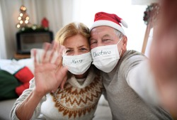 Front view of senior couple with face masks indoors at home at Christmas, taking selfie.
