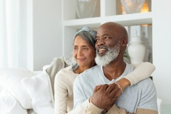 Front view of senior diverse couple sitting on a white couch in beach house. Authentic Senior Retired Life Concept