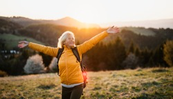 Front view of senior woman hiker standing outdoors in nature at sunset.
