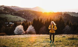 Front view of senior woman hiker walking outdoors in nature at sunset.