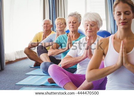 Front view of seniors relaxing with fitness instructor in retirement house