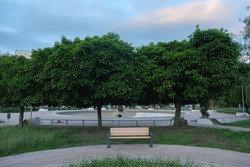 Front view of single orange wooden bench in the city park without a people.
