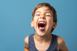 Front view of small caucasian boy four years old standing in front of blue background studio shot playful child making faces happiness and joy concept