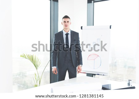 Front view of smart ambitious young manager standing in his office and looking at camera
