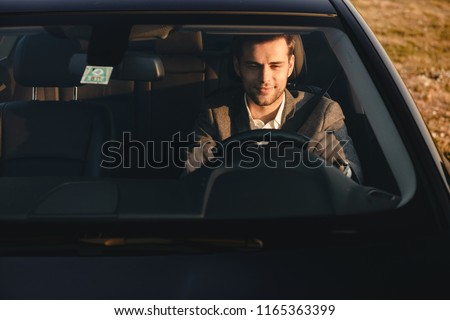 Front view of smiling bussinesman in suit driving his car