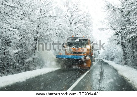 Front view of snowplow service truck and  gritter spreading salt on the road surface to prevent icing in stormy snow winter day.