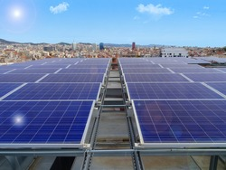 front view of solar panels on a rooftop overlooking the Barcelona skyline on a sunny day with a blue sky and solar glare effects