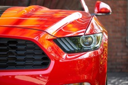 Front view of sportscar with brick wall. Concept of car detailing and paint protection background. Clos up of headlight detail of modern luxury car with reflection on red paint after wash & wax.