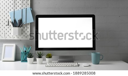 Front view of stylish workspace with mock up computer and office supplies gadget. Blank screen for graphic display montage.