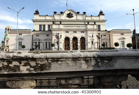 front view of the Bulgarian parliament through an old stone fence