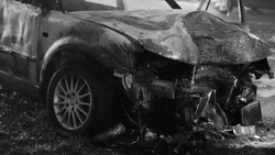 Front view of the car burned after the serious car accident at night in winter. Black and white. High quality photo