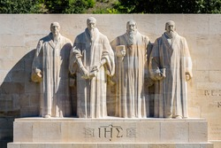 Front view of the four statues at the center of the Reformation Wall in the Parc des Bastions in Geneva, Switzerland, representing John Calvin and the Calvinism's main proponents, on a sunny day.