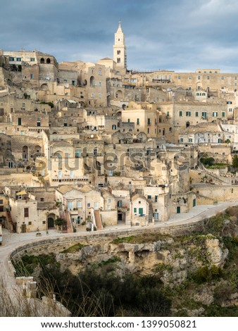 Front View of the Italian traditional village of Matera, with its road and its ancient walls, next to its ravine, under a cloudy sky