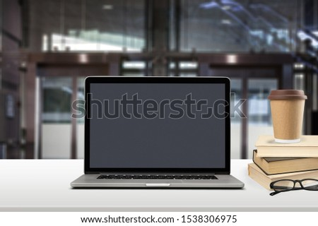 Front view of the laptop on the work desk on background blur of office,blank screen for graphics display montage.- Image- Image