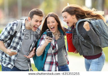 Front view of three excited students receiving good news on line in a mobile phone in an university campus or street