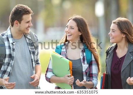 Front view of three students walking and talking in an university campus #635351075