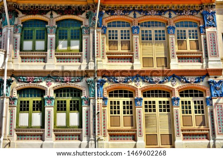 Front view of traditional Straits Chinese or Peranakan Singapore shop house exteriors with arched windows, antique wooden shutters and colourful exterior in Jalan Besar, Singapore