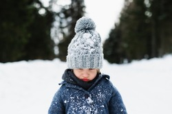Front view of unhappy small child standing in snow, holiday in winter nature.