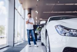 front view of white car in dealership salon with pensive man on the background, blurred shot