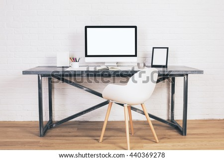 Front view of white chair and designer desk with blank laptop and picture frame on wooden floor and brick background. Mock up