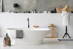 Front view of white modern bath in contemporary apartment with stylish loft interior design, house decor, cotton bathrobe and clean dry towels