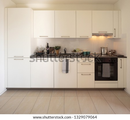 Front view of white modern kitchen with lights on. Nobody inside #1329079064