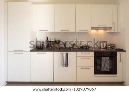 Front view of white modern kitchen with lights on. Nobody inside #1329079067