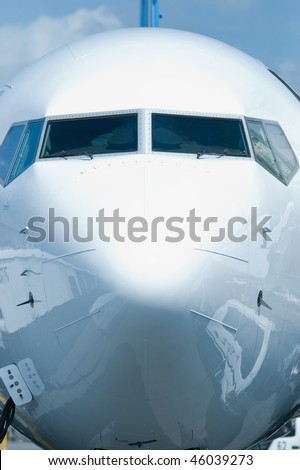 Front view of white passenger airplane with ground equipment reflected in the hull.