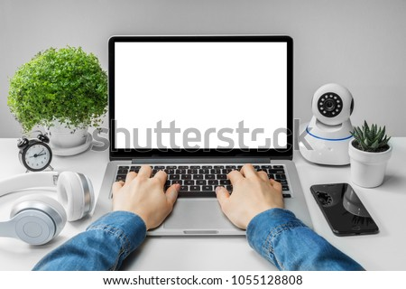 Front view of woman hands working on laptop with blank white screen standing on the white office desk with smartphone and web- camera. Mock up, copy space for your text.