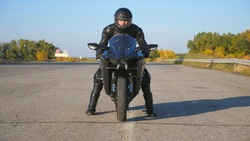 Front view of young biker in helmet and leather jacket is sitting on motorcycle at highway road and ready to ride. Man is going to ride at sport motorbike. Concept of freedom and adventure. Close up.