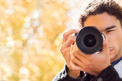 Front view of young male photographer taking pictures in autumn forest