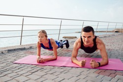 Front view of young sportswoman and sportsman doing push ups on elbows, during workout near the sea. Sport concept.