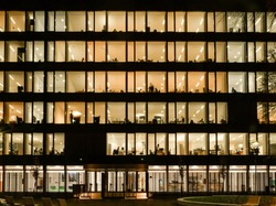 Front view on illuminated offices of a corporate building with people working overtime. Long exposure at night.