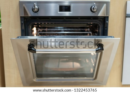 Front view photo of open door on new and modern built-in oven #1322453765