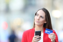 Front view portrait of a doubtful woman in red holding credit card and cell phone looking at side wondering if buy