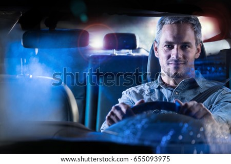 Front view. Portrait of a handsome man driving his car at night in the rain. The traffic lights behind him