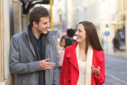 Front view portrait of a happy couple walking in the street having a conversation