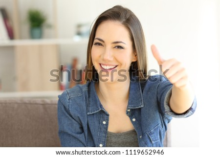 Front view portrait of a happy woman gesturing thumbs up sitting on a couch in the living room at home