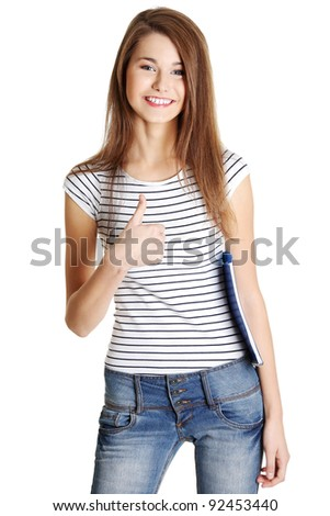 Front view portrait of a young happy female caucasian student holding a notebook and giving a thumb-up, on white.