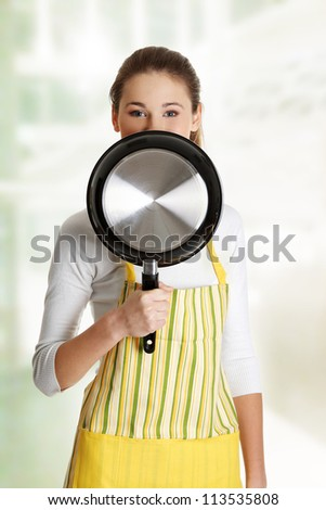 Front view portrait of a young smiling caucasian female teen dressed in apron, smiling behind the frying pan.