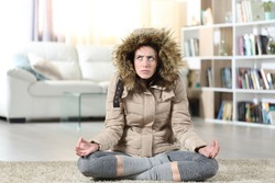 Front view portrait of an angry woman with damaged heater at home trying to relax doing yoga exercise