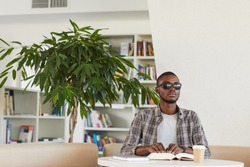 Front view portrait of blind African-American man reading Braille book in library, copy space