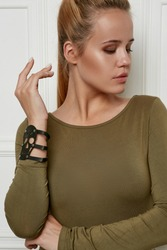 Front view portrait of lady with fair hair, wearing olive sweater. The woman is turning head to side, wearing leather slave bracelet with silver ring and studs with wide insertion in view of skull.