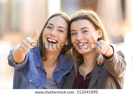 Front view portrait of two funny friends with thumbs up and looking to the camera in the street