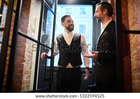 Front view portrait of two handsome gentlemen entering cafe chatting cheerfully, copy space #1322594525