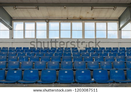 Front view row of blue plastic seats on rough concrete step floor in old vintage dirty concrete structural stadium with windows frame background without people.