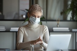 Front view 30s businesswoman wearing protective medical facemask sitting at table with laptop, disinfecting hands before starting working remotely from home, healthcare habit stop spreading virus.