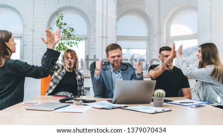 Front view shot of five happy business people celebrating success giving high five to each other, looking excited after signing profitable contract. Teamwork concept.