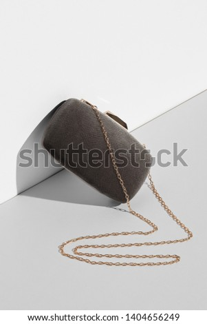 Front view shot of taupe clutch covered with suede, adorned with golden clasp fastener. The accessory with snake-like placed chain strap is angled on white platform. Fashionable women's accessory. #1404656249